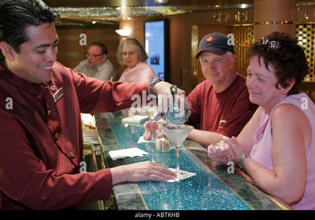 Puerto Rico Atlantic Ocean Holland America Line ms Noordam Atrium Bar Asian male bartender couple mix drink - Stock Image