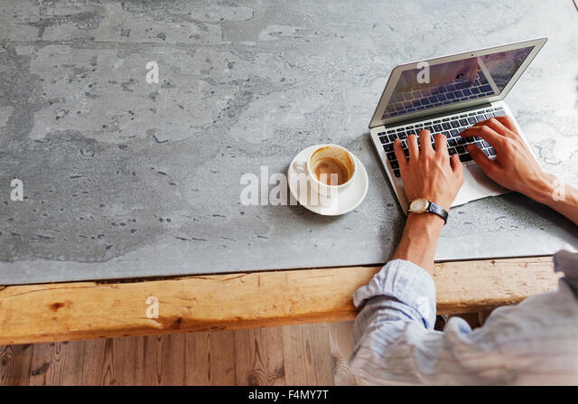 High angle view of man using laptop at restaurant - Stock Image