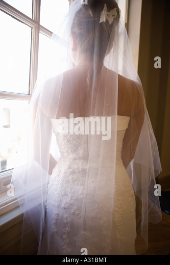 Bride looking out of window - Stock-Bilder