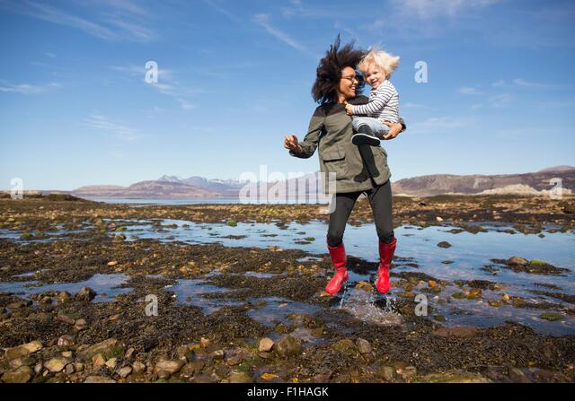 Mother holding son jumping in Loch Eishort, Isle of Skye, Hebrides, Scotland - Stock Image