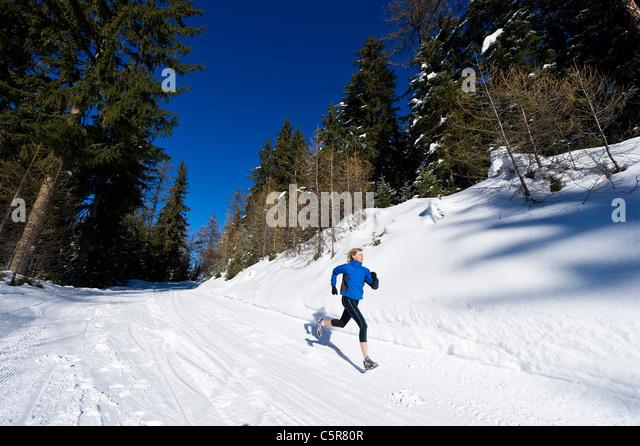 A jogger runs through an alpine forest. - Stock-Bilder