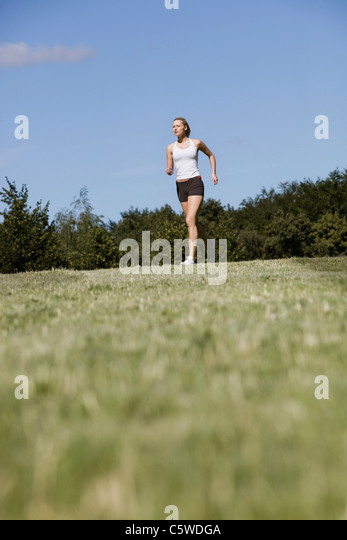 Germany, Berlin, Young woman jogging - Stock Image