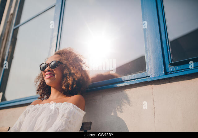 Outdoor shot of happy young african female sitting outdoors and smiling. Woman wearing sunglasses sitting outside - Stock Image
