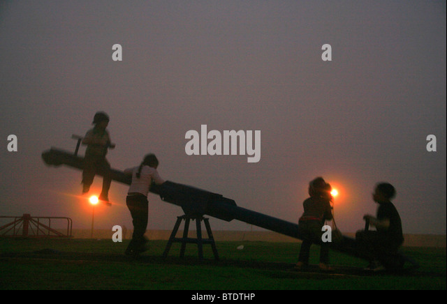 Children playing on playground in the mist - Stock Image