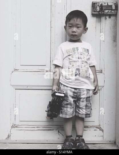 Boy in front of a door. - Stock-Bilder