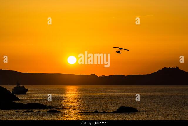 Flying boat in a fabulous orange sunset over Sardinia, Italy - Stock Image