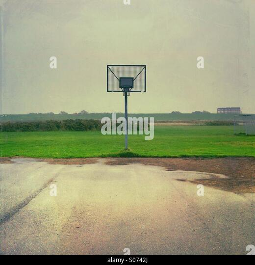 Empty wet basketball court on a grey rainy day near Husum, Nordfriesland, Schleswig-Holstein, Germany - Stock Image