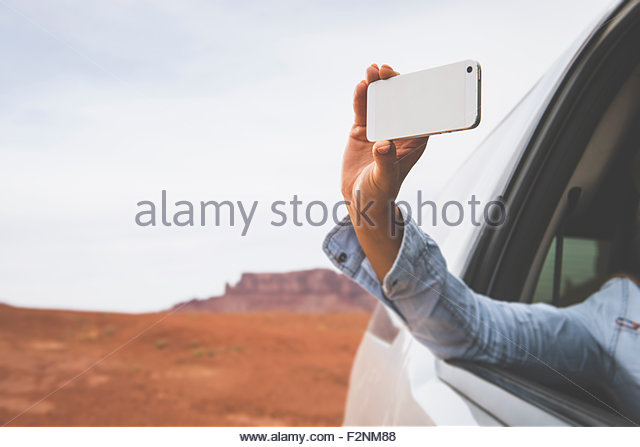Caucasian woman photographing Monument Valley, Utah, United States - Stock Image