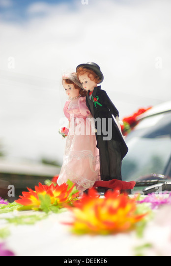 Miniature smart couple based on front car ready for wedding with flowers on their feet - Stock-Bilder