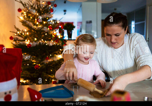 Mother and daughter rolling dough at table during Christmas - Stock-Bilder