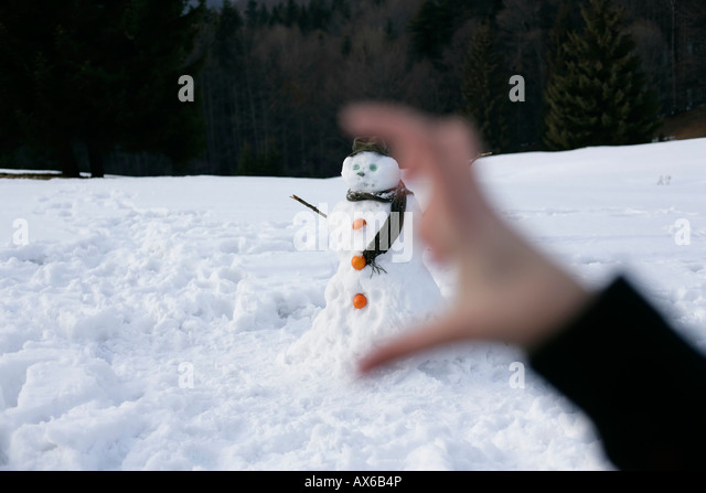 View through two fingers to a snowman - Stock Image