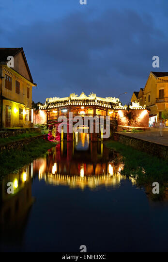 Japanese Covered Bridge reflected on canal, Hoi An, Vietnam - Stock Image