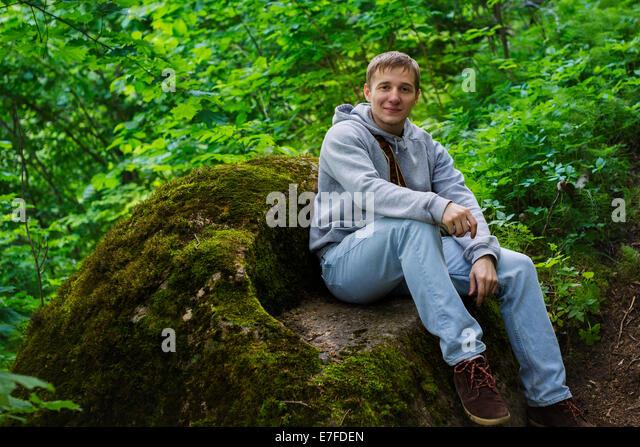 Handsome man sitting on a rock - Stock-Bilder