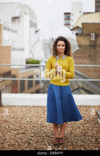 Female office worker on rooftop holding umbrella - Stock Image