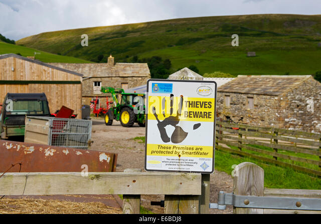 Sign warning about farm thieves, on gate to farm in Swaledale, Yorkshire Dales National Park, North Yorkshire, England - Stock Image