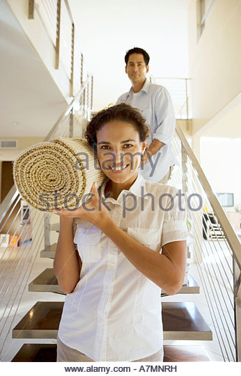 Couple moving house carrying rolled up carpet on shoulders down staircase front view smiling portrait - Stock-Bilder