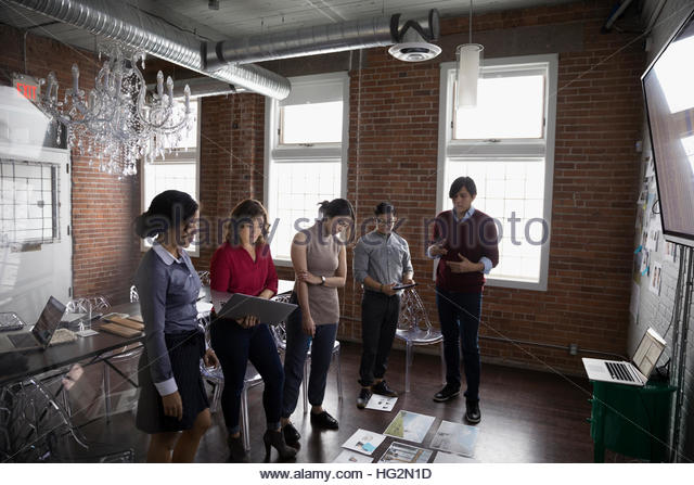 Hispanic designers meeting and brainstorming reviewing proofs in conference room - Stock Image