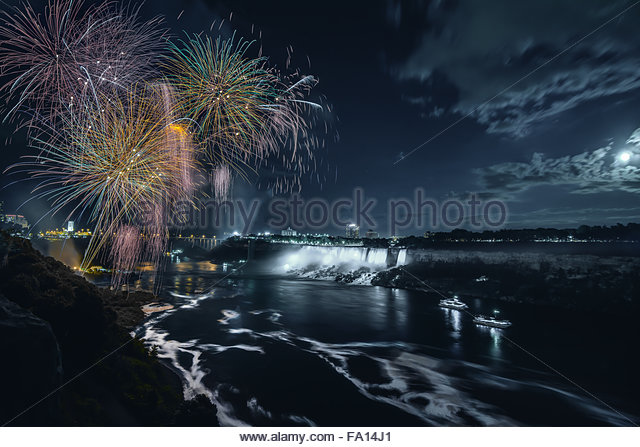 A moonlit fireworks celebration at Niagara Falls Ontario Canada at night showing the falls the motion in the river - Stock Image