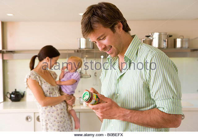 Young couple in kitchen, pregnant woman with baby girl 6-9 months, man looking at baby food label - Stock Image