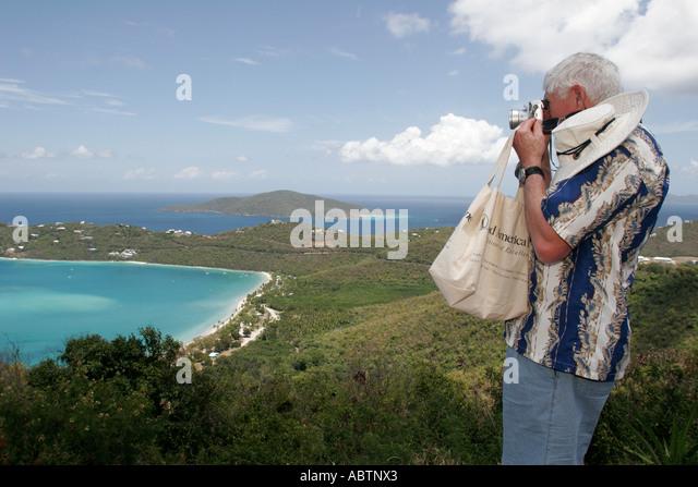 St. Thomas USVI North Side Skyline Drive Megans Bay and Beach Atlantic Ocean senior male camera - Stock Image