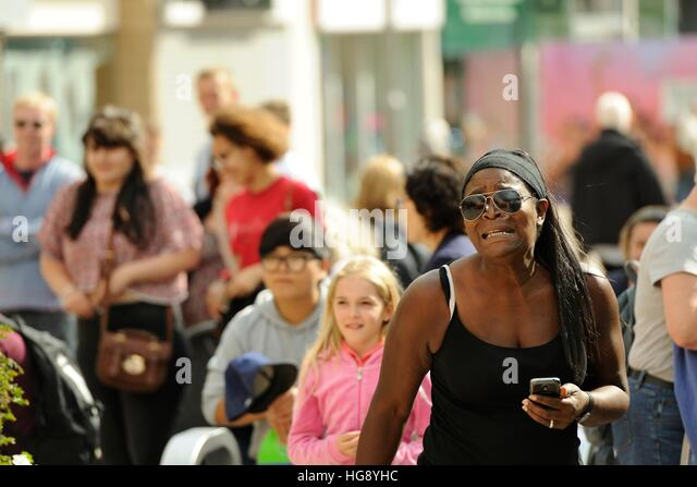 Afro-Caribbean woman and blond girl watching musicians on the Moor Sheffield, taking part in the Tramlines Festival - Stock Image