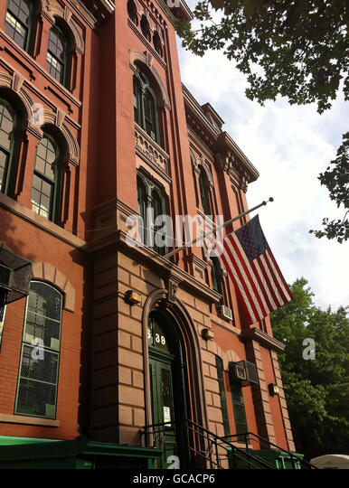 School building with US flag in Brooklyn, New York. - Stock Image