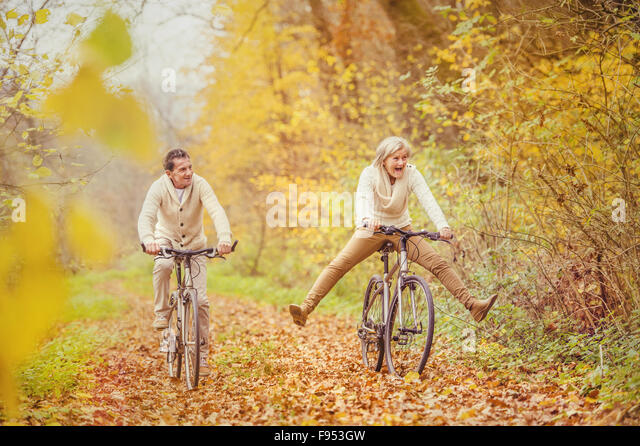 Active seniors riding bike in autumn nature. They having fun outdoor. - Stock Image