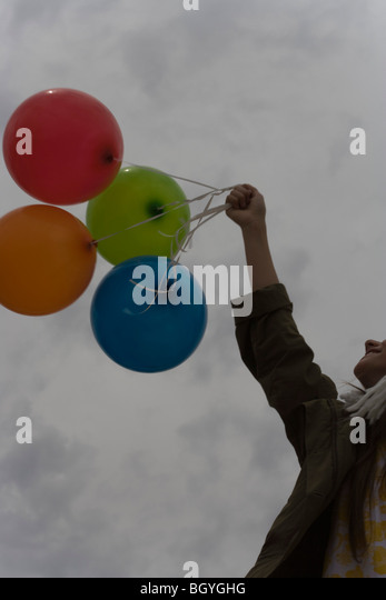 Female holding bunch of balloons up towards cloudy sky - Stock Image