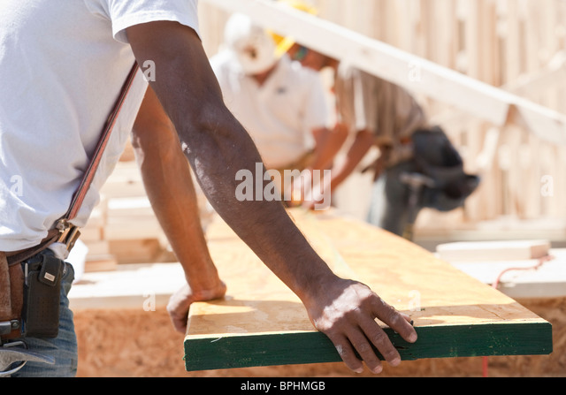 Carpenters holding a plank at a construction site - Stock Image