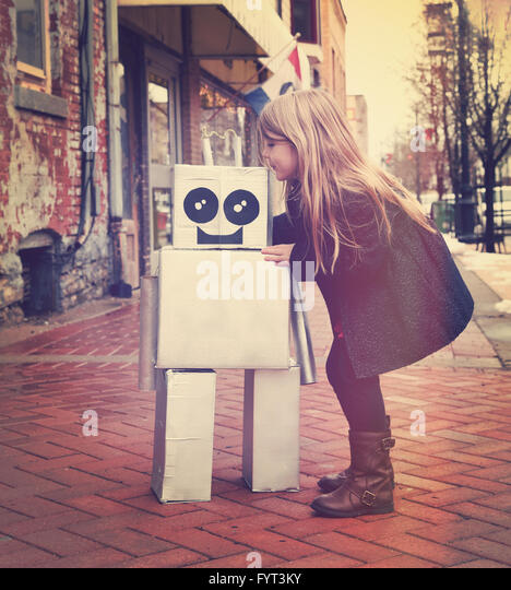 A little girl is hugging a metal cardboard robot downtown against a brick wall outside for a friendship or inventor - Stock Image