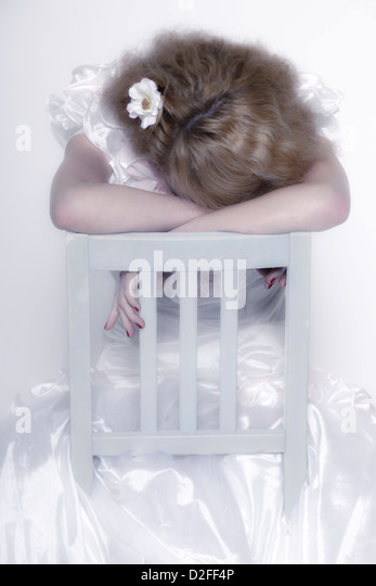 a woman in a white dress is sitting on a white chair and is crying - Stock Image
