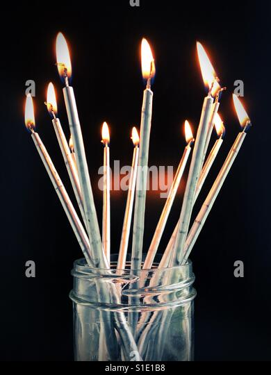 Long thin candles in a jar. - Stock Image