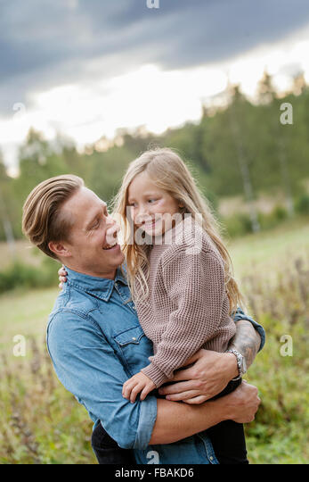 Finland, Uusimaa, Raasepori, Karjaa, Father holding his daughter (6-7) - Stock Image