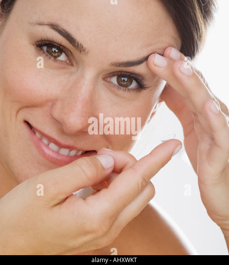 Woman putting in contact lens - Stock Image