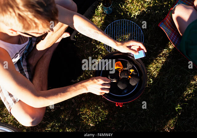 High angle view of man preparing barbeque at picnic - Stock Image
