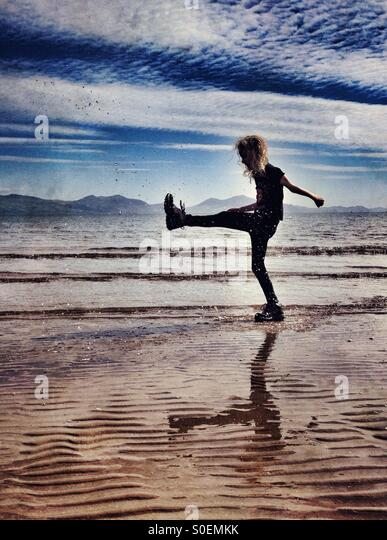 Young girl playing in sea at Newborough beach on Anglesey - Stock Image