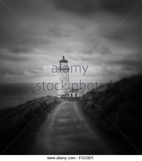 Footpath And Lighthouse, Horizon Over Sea, Moody Sky - Stock Image
