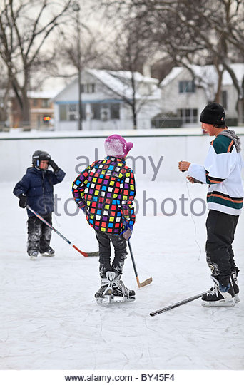 Boys on an outdoor ice hockey rink,  Winnipeg, Manitoba, Canada - Stock Image