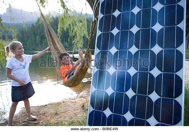 Girl pushing brother 5-9 in hammock by lake, solar panel in foreground, portrait of boy - Stock Image