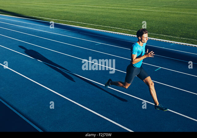 Shot of a young male athlete training on a race track. Sprinter running on athletics tracks. - Stock-Bilder