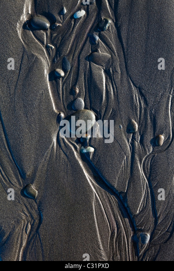 Water and rounded pebbles form abstract designs in the sand at Kalaloch Beach, Olympic National Park, Washington. - Stock Image