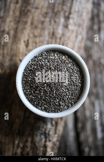 Chia seeds in a white bowl on a wooden table - Stock Image
