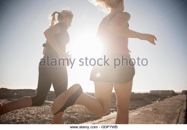 Two young female runners running along sunlit coast, Seapoint, Cape Town, South Africa - Stock Image