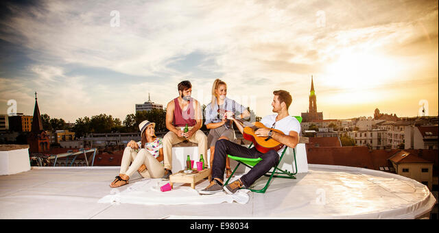 Young people listening to guitar music at rooftop party - Stock Image