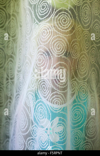 Sweden, Narke, Filipshyttan, Portrait of girl (4-5) hiding behind curtain - Stock Image
