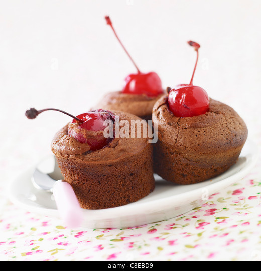 Individual chocolate and Amarena cherry soft cakes - Stock Image