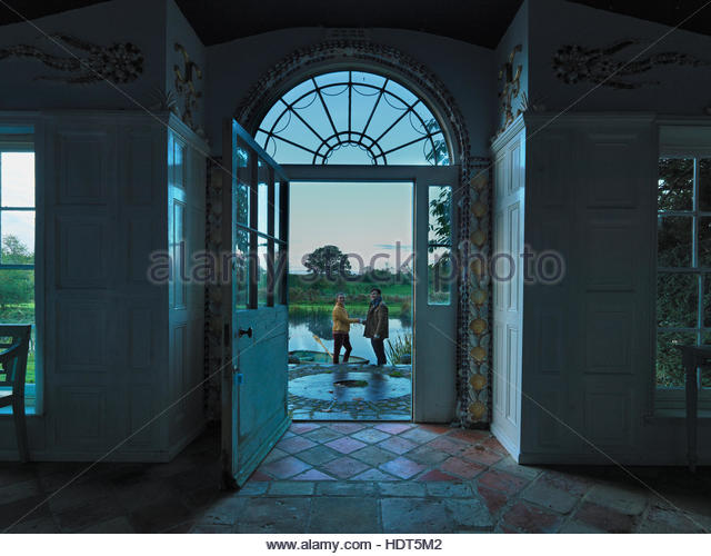 Young couple in front door of stone building. - Stock Image