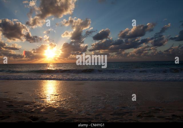 Sunset and sea washing over beach, Grand Cayman, Cayman Islands - Stock Image
