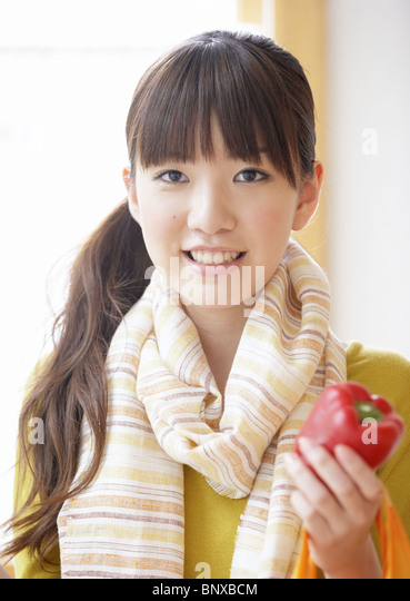 Young woman holding a bell pepper - Stock Image