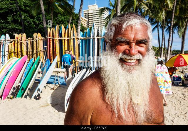 Hawaii Hawaiian Honolulu Waikiki Beach resort Kuhio Beach State Park man long white beard surfer rental surfboards - Stock Image